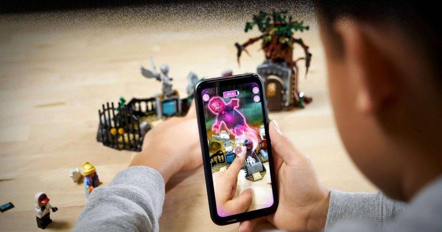 Un niño jugando con un móvil y el set del cementerio de Lego hidden side