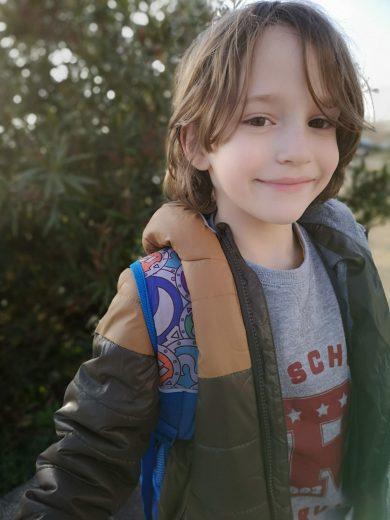 Mi hijo Alejandro en la calle, en invierno, con una mochila