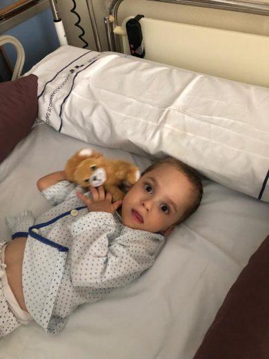Niño en cama de hospital con un oso de peluche