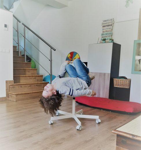 Alejandro sentado boca arriba en una silla giratoria, presa del aburrimiento