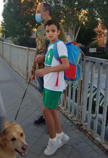 Rodrigo de pie con la mochila puesta cogido de la mano de su padre, con cara de no estar muy convencidopar la Vuelta al cole