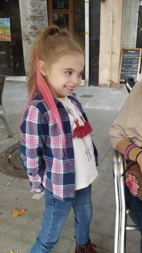 Una niña de pie con mechas rosas, camisa a cuadros sobre una camiseta blanca y vaqueros