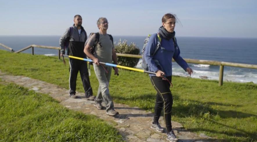 Tres personas hacen el camino de santiago sujetas a un bastón alargado ya que una de ellas es ciega. Cine inclusivo