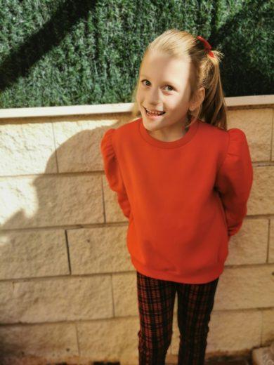 Niña rubia con jersey rojo de pie. Síndrome de Angelman.