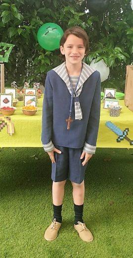 Alejandro con traje de comunión en un jardín