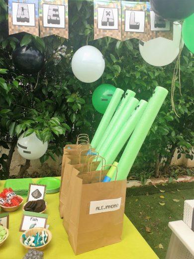 Bolsas de papale marrón de regalo sobre una mesa. Sobresalen churros de piscina verdes