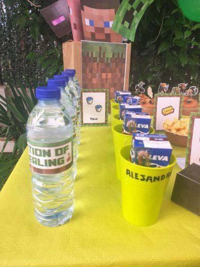 Mesa dulce con vasos verdes y botellas de agua