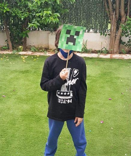 Alejandro con una máscara verde al aire libre. Hay césped