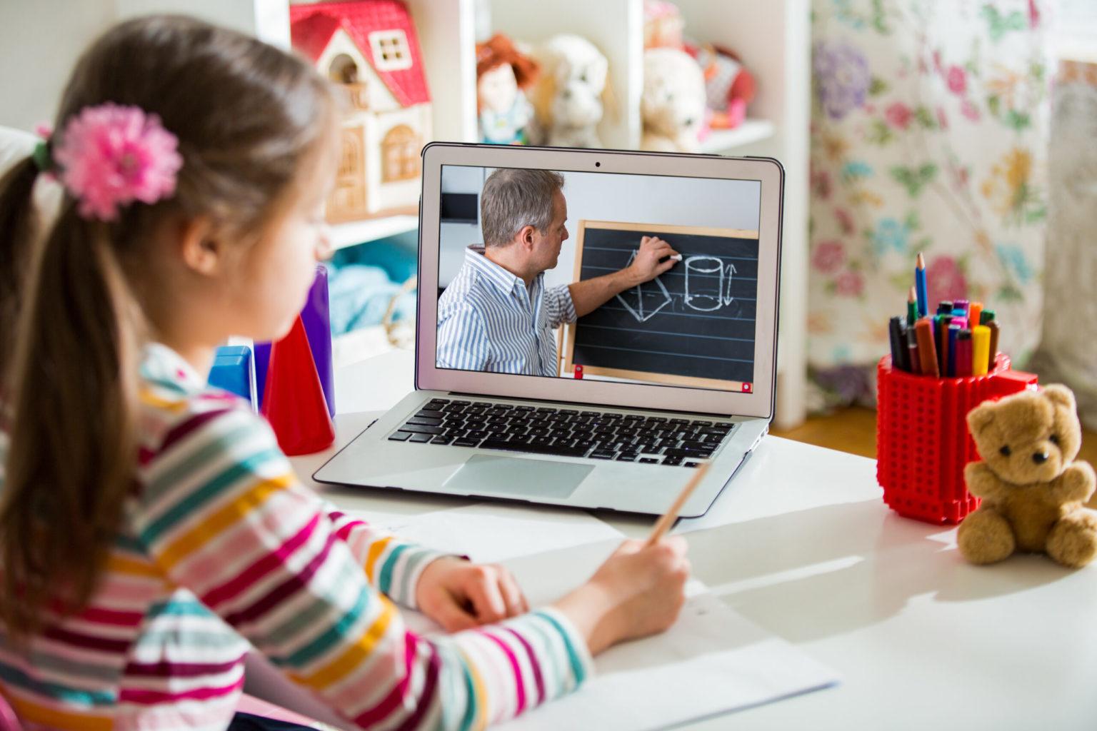 Nila dando clase online. LLeva dos coletas con pompones rosas y un jersey de manga larga a rayas de colores