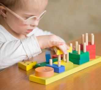 Niña pequeña con gafas jugando con unos encajables basados en la pedagogía Montessori Son pieezas geométricas de colores hechas en madrea y hay que insertarlas